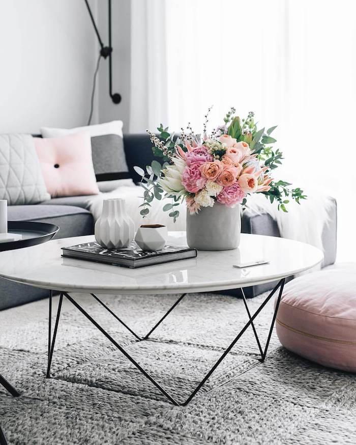 dekoartikel wohnzimmer, runder weißer kaffeetisch, geometrische vasen, viele blumen
