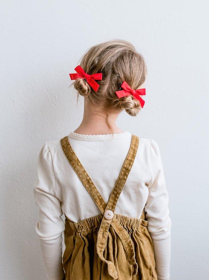 Double Bun mit zwei roten Schleifen, brauner Jumpsuit und weiße Bluse mit langen Ärmeln