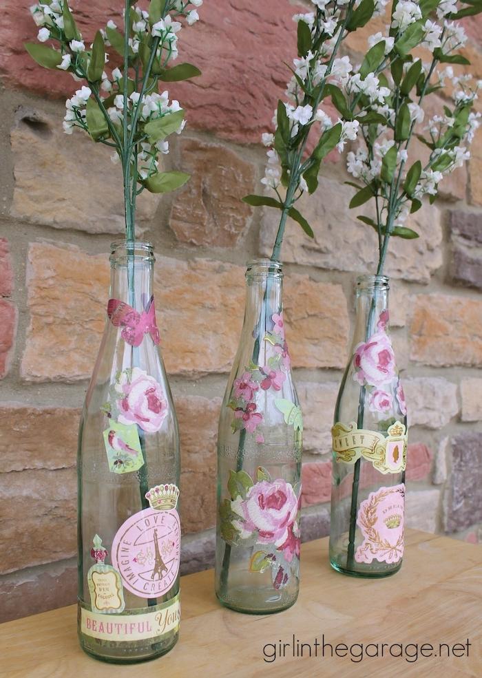 eine wand mit steinen und drei flaschen mit decoupage mit pinken servietten mit pinken fliegenden schmetterlingen und pinken rosen, vasen mit weißen blumen und mit grünen blättern, altee flaschen recyceln ideen diy