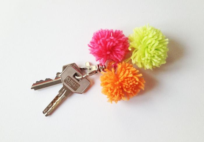 drei Quasten in rosa, grüner und oranger Farbe mit zwei Schlüssel, Schlüsselband selber machen
