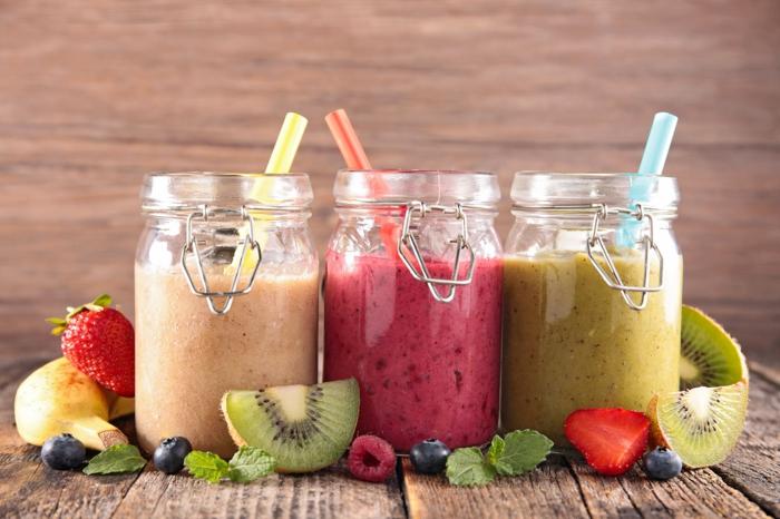 drei Smoothies aus drei Fruchtsorten mit Trinkhalmen, Diät Essen zum Frühstück