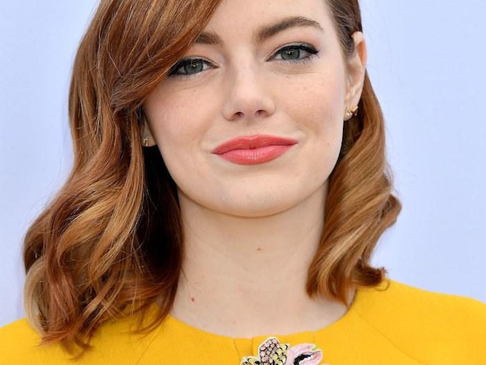 Emma Stone Haarfarbe, mittellange wellige Haare, Koralle Lippenstift und schwarzer Eyeliner