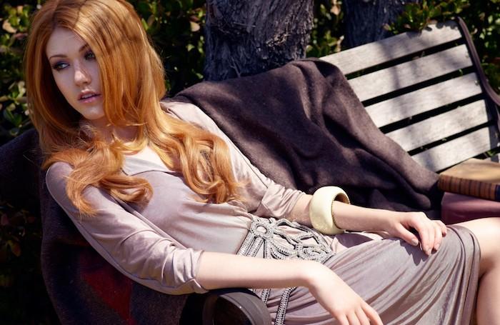 Goldbraune wellige Haare mit Mittelscheitel, heller Hautteint, Kleid mit langen Ärmeln in Beige