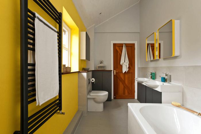 badezimmer sterichen ideen, eine weiße badewanne in einem badezimmer mit gelben und weißen wänden und mit weißen badmöbeln und einer tür aus holz