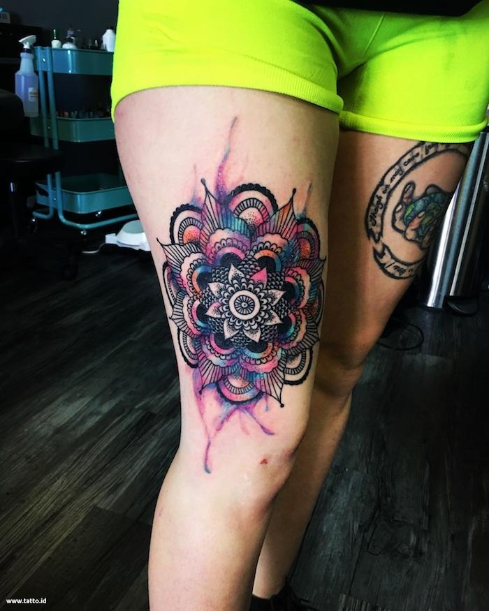boden aus holz und eine frau mit tätowierten beinen, ein bein mit einem großen violetten watercolor tattoo mandala mit mandala blumen