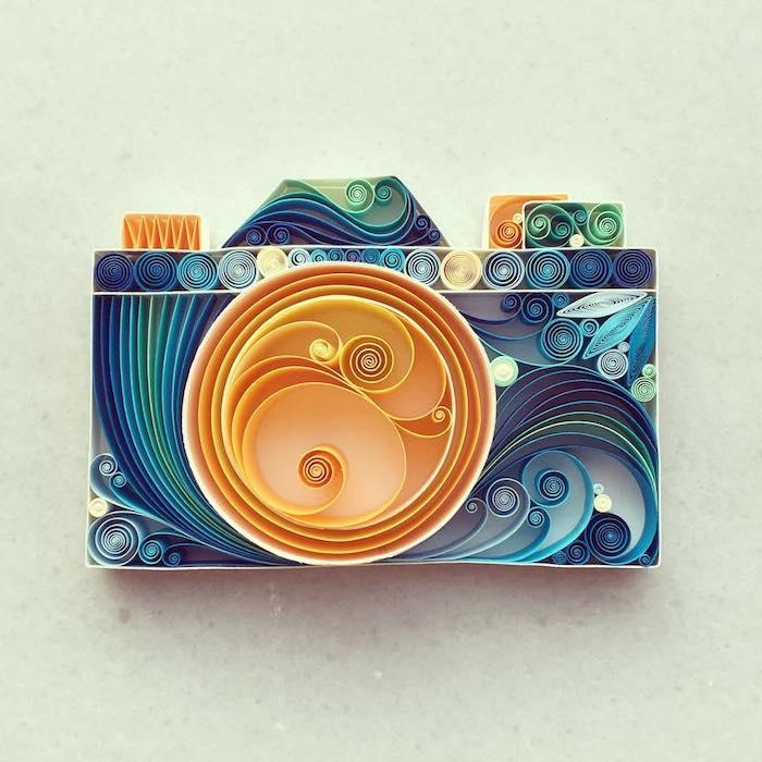 ein kleines blaues fotoapparat aus langen blauen und gelben und grünen gefalteten quilling papierstreifen, basteln mit kindern, recycling basteln