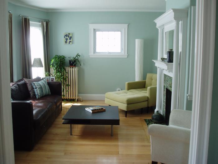 ein boden aus holz und ein wohnzimmer mit weißen und grünen und braunen sofas und mit einem kleinen schwarzen tisch und grünen wänden, wohnzimmer streichen ideen