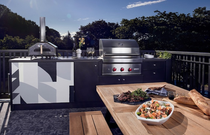 blauer himmel und eine schwarze außenküche mit einem ofen und einem elektroherd und bbq, ein brauner tisch aus holz