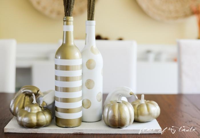 ein brauner tisch aus holz und eine tischdeko mit kleinen goldenen kürbissen und eine r goldenen flasche und einer weißen alten weinflasche, vasen aus alten flaschen basteln