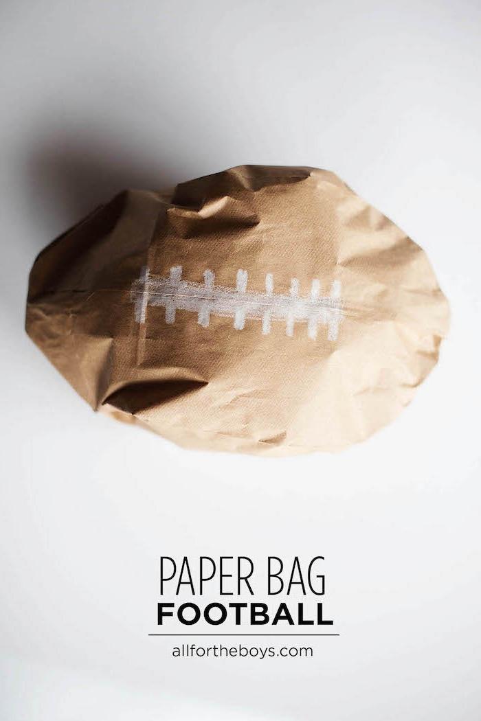kleines braunes ball aus einer alten gefalteten tüte aus einem braunen alten papier und mit einer weißen baumwolle