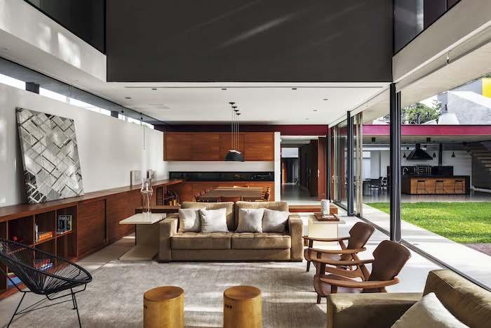 braune stühle aus holz und braune sofas mit weißen kissen und ein teppich, eine outdoor küche in einem garten mit einem grünen rasen