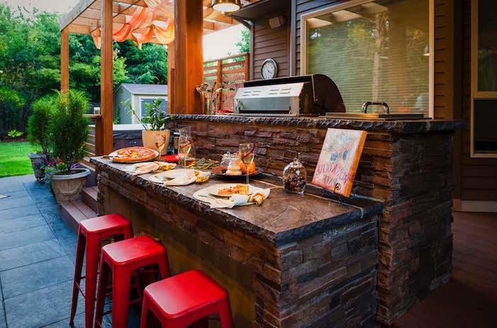 drei rote stühle und eine kleine braune miniküche ,miteinem grill, herd und einem waschbecken, ei garten mit grünen pflanzen