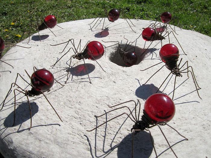 ein grauer tisch aus stein und viele große rote dekorative ameisen aus alten roten glühbirnen und mit langen schwarzen beinen, garten deko selber basteln, recycling bastreln ideen