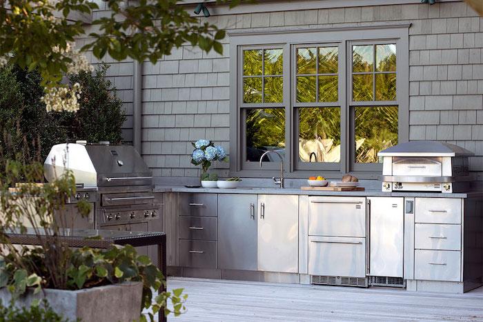 ein weißer boden aus holz unn ein graues haus mit grauen wänden und fenstern, eine außenküche selber bauen, eine küche mit einem waschbecken und elektroherd und einem ofen