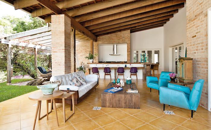 ein brauenr noden aus braunen fliesen, ein garten mit einem grünen rasen, eine küche mit einem waschbecken und elektroherd und einem ofen , eine außenküche selber bauen, blaue und weiße sofas und violette stühle