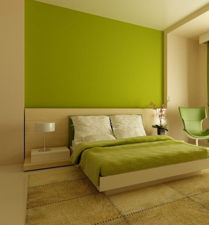 ein bett mit einer grünen decke und grünen kissen und eine schwarze vase mit pinken blumen, ein grüner stuhl und eine kleinen weiße lampe, wandfarbe grün schlafzimmer