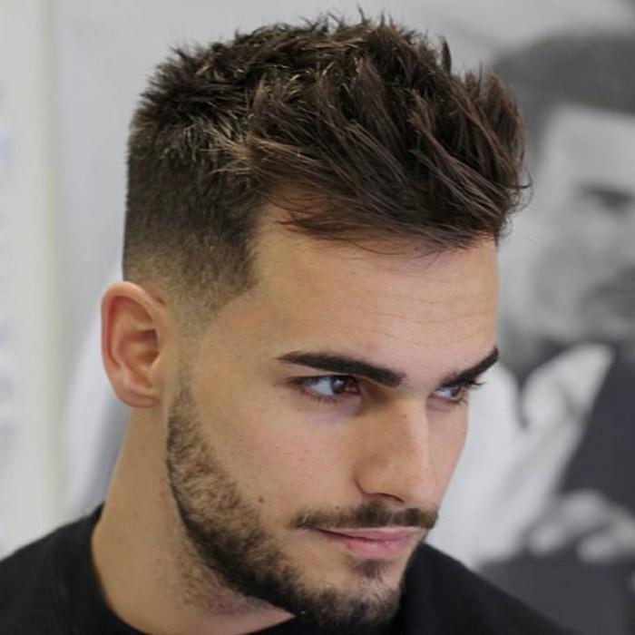 ein Junge mit braunem Haar, kurzer Bart, Igelfrisur in der Mitte, Etagenschnitt, Kurzhaarausschnitt Männer