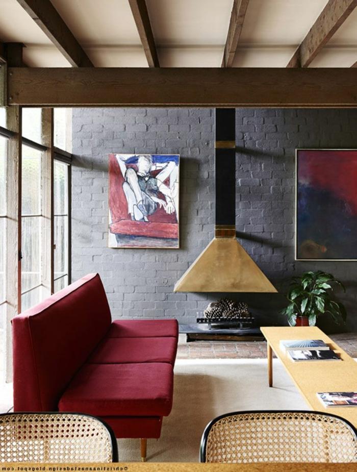 eine graue Wand, ein rotes Sofa, ein Kamin, ein Tisch, welche Farbe passt zu Grau