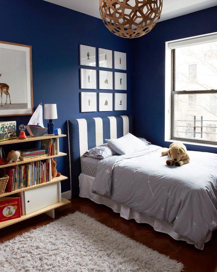 ein bett mit einer blauen decke mit weißen sternen und mit blauen kissen und einem kuschektier, regale mit vielen büchern, ein kinderzimmer einrichten, wandfarbe blau