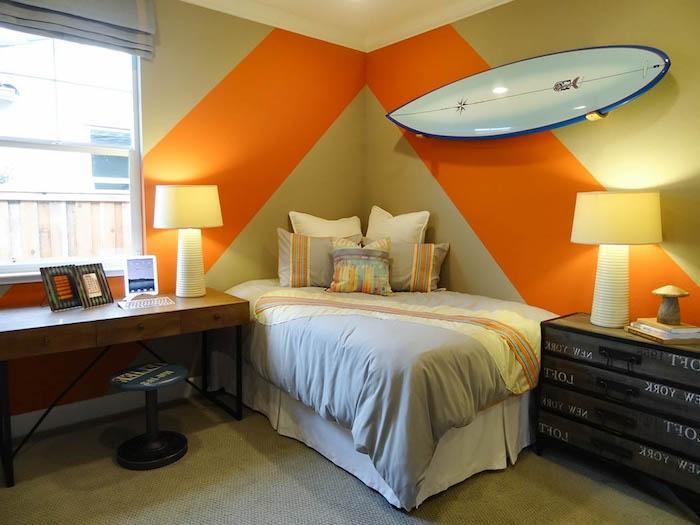 ein bett mit weißen kissen und einer blauen deckem eine orange wand und ein brauner schreibtisch aus holz und zwei kleine weiße lampen und ein fenster, wand farbig streichen