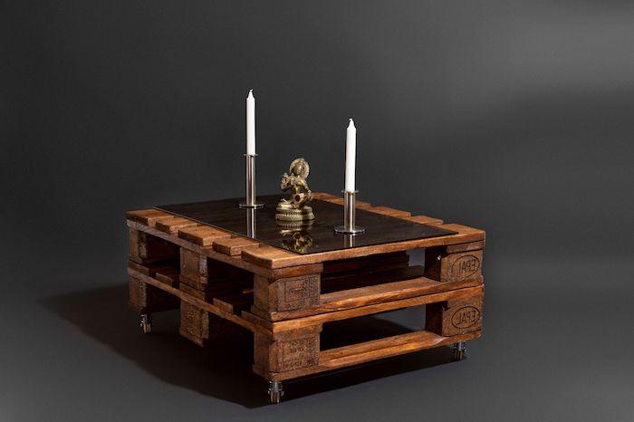 ein kleiner brauner tisch aus braunen europaletten aus holz und mit zwei weißen langen kerzen und eine schwarze wand