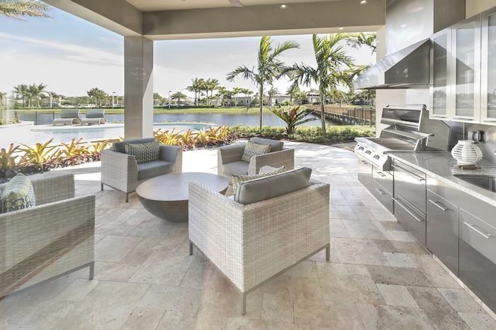 ein großes blaues schwimmpool und viele grüne palmen und ein blauer himmel, eine outdoor küche mit einem waschbecken und elektroherd und einem grauen ofen und viele weiße sofas aus rattan