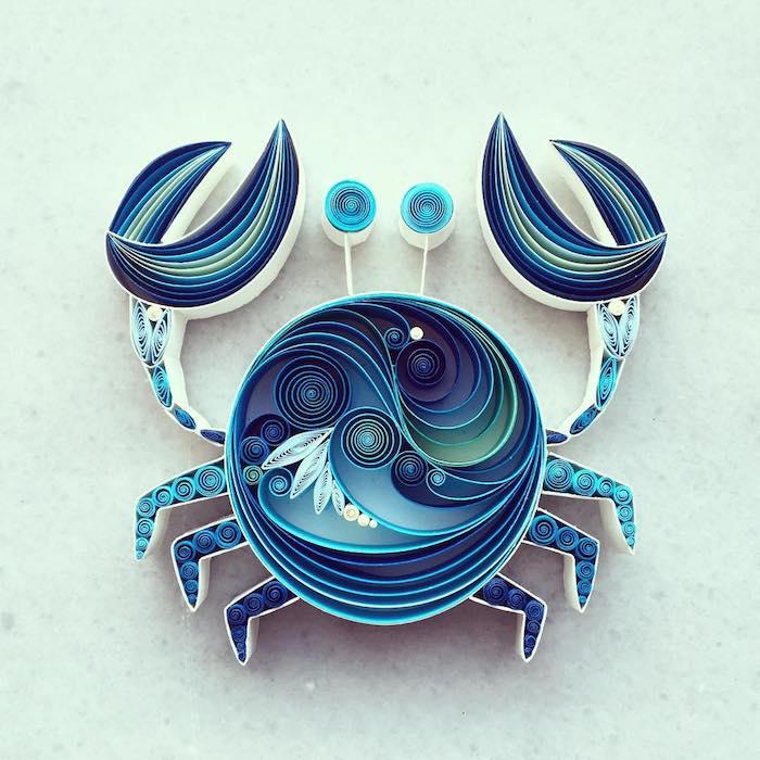 upcycling ideen diy, eine quilling figur mit einem blauen krebst aus vielen langen gefalteten blauen und weißen papierstreifen und mit blauen augen