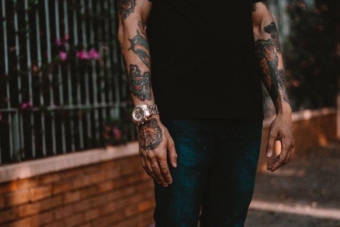 violette blumen und ein mann mit einer hand mit einer wei0en armbanduhr, hände mit vielen farbigen aquarell tattoos für männer
