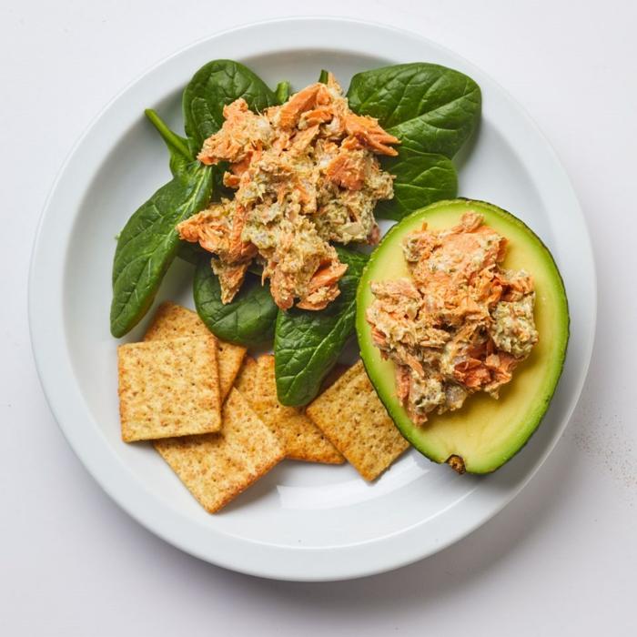 Avocado Salat, ein Stück Avocado, Crakers, ein Gemisch aus Fisch und Majo