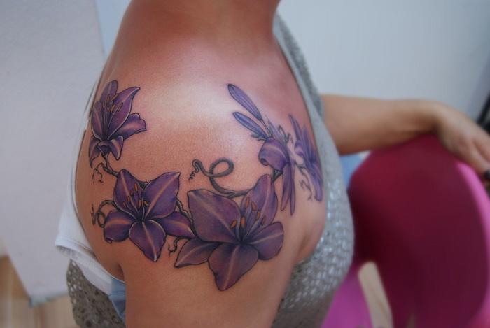 eine junge frau mit einem großen violetten watercolor tattoo arm mit vielen violetten und gelben blumen, frau und ein pinker stuhl