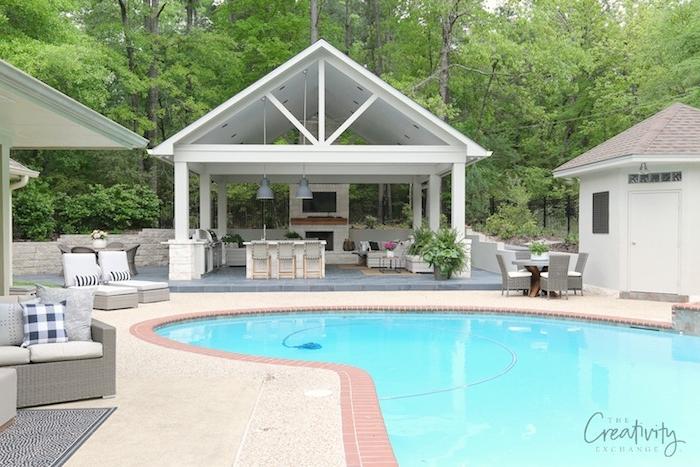 ein blaues pool und ein garten mit einem grünen wald mit grünen bäumen, küche mit einem waschbecken und elektroherd und einem ofen und mit grauen lampen, eine außenküche selber bauen, sofas und stühle aus rattan