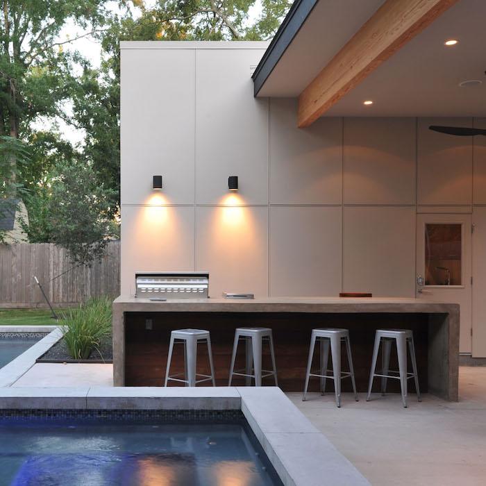 garten mit grünen bäumen und ein weißes pool und eine küche mit viele grauen stühlen und einem kleinen grauen backofen und zwei lampen
