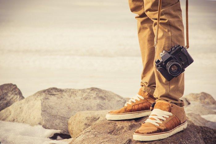 meer und ein strand mit steinen und ein reisender mann mit braunen schuhen und ein schwarzer fotoapparat