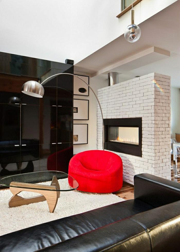 ein Kamin, ein roter Sessel, weißer Teppich, schwarze Wand, gläserner Tisch, schöne Farbkombination