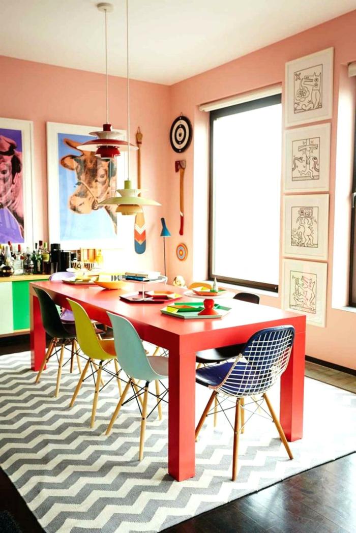 roter Tisch, rosa Wandfarbe Küche, bunte Stühle, jeder in verschiedener Farbe
