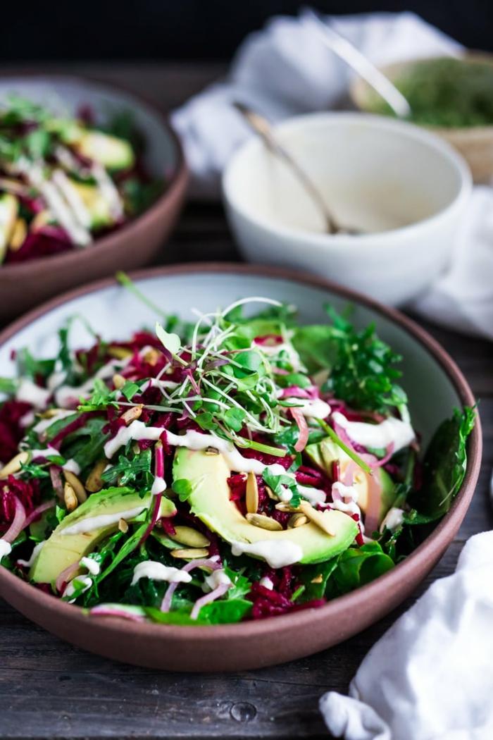 eine lila Schale, Avocado im Salat, roter Zwiebel, Salatblätter, Kohl