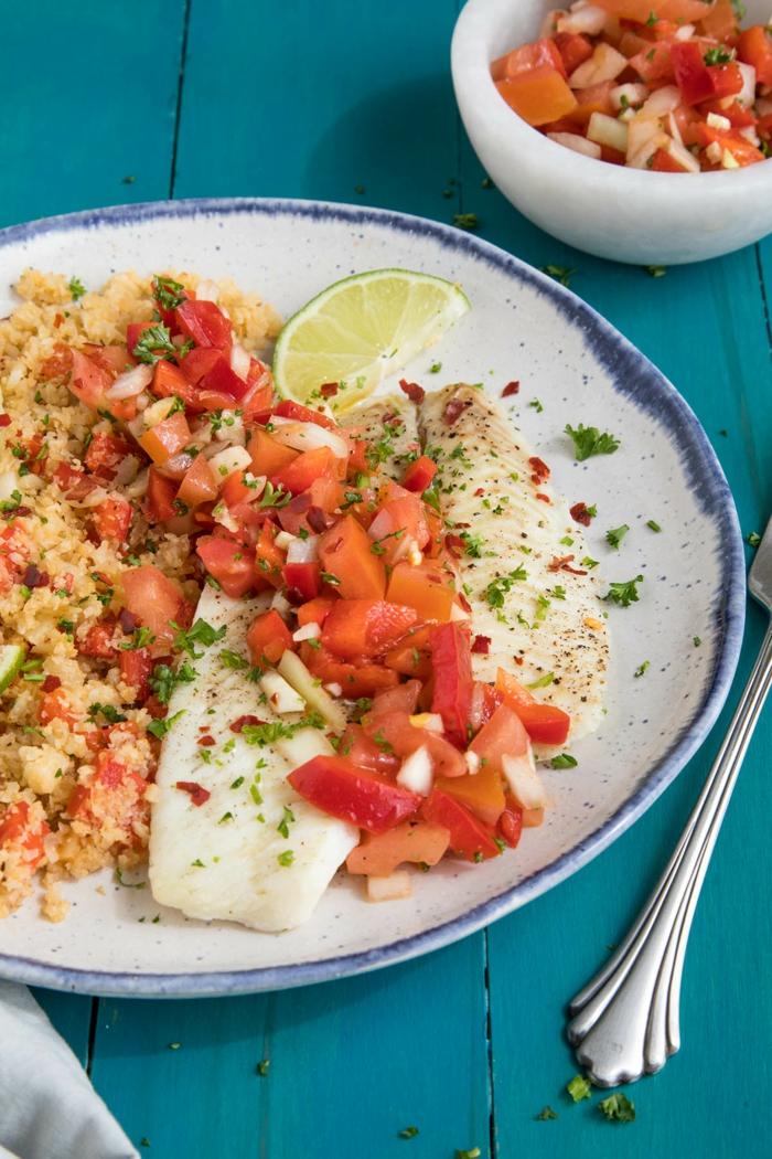 ein Gericht mit Fischfillet, Paprika und Tomaten, Zitronen als Beilage, Gerichte zum Abnehmen