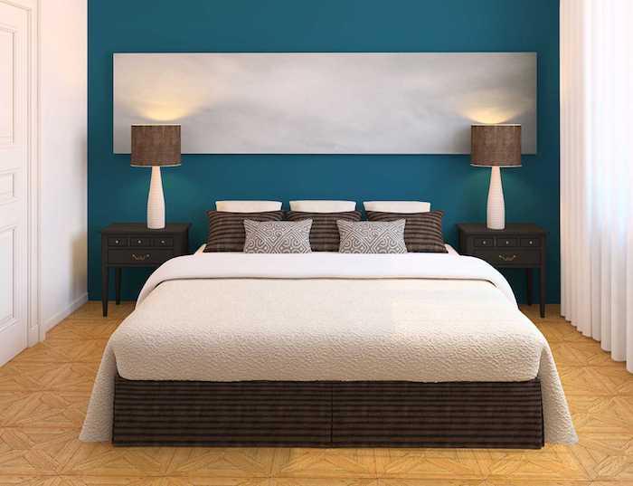 wandfarbe schlafzimmer, ein schlafzimmer mit einer blauen wand und mit einem bett mit braunen und weißen kisse, wand streichen ideen schlafzimmer