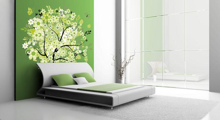 ein schlafzimmer mit einer grünen wand mit einem schwarzen baum mit weißen und grünen blumen, wandfarbe grün schlafzimmer, wand streichen ideen, bett mit grünen kissen