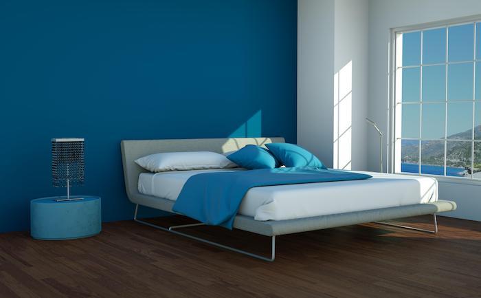 eine weiße wand mit fenster in einem schlafzimmer mit einem bett mit weißen und blauen kissen und mit einem braunen boden aus holz und einer blauen wand