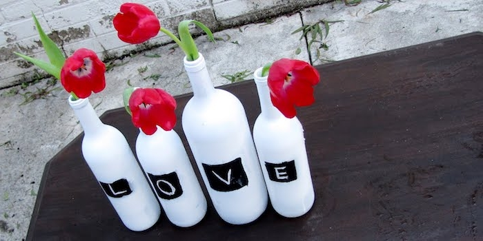 ein schwarzer tisch und eine tischdeko mit vier weißen flaschen, vasen aus flaschen und mkt vier roten tulpen mit grüne langen blättern