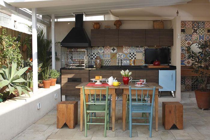 kleine braune blumentöpfe mit grünen pflanzen, eine außenküche selber bauen ideen, ein brauner tisch aus hilz und blaue und grüne stühle