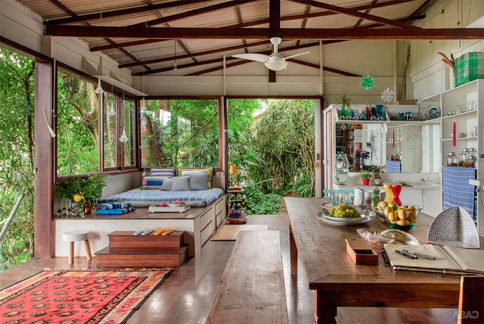 ein rotter teppich und eein brauner tisch aus holz, ein brauner boden und sofas mit kissen, eine außenküche selber bauen ideen