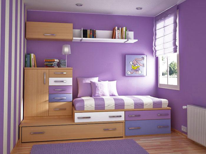 kinderzimmer mit violetten wänden und mit möbeln aus holz und vielen büchern, ein kinderbett mit weißen und violetten kissenn, aubergine farbe