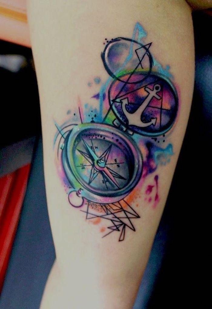 ein großes tattoo aquarell mit einem bunten kompass und mit einem kleinen weißen anker tattoo, frauen tattoo watercolor