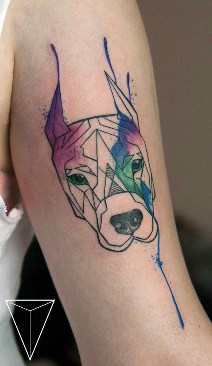 eine hand mit einem großen bunten tattoo aquarell mit einem hund mit einer schwarzen nase und mit grünen augen, hund tattoo arm