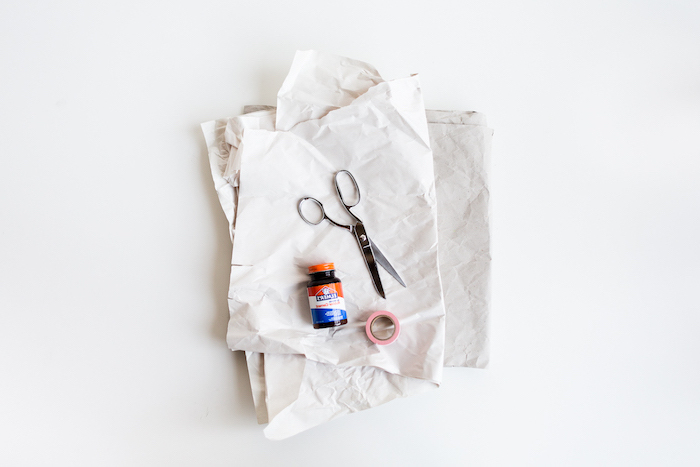 eine schere aus metall und kleber und eine geschnittene alte weiße papiertüte, materiallien für einen diy blumentopf aus einer papiertüte