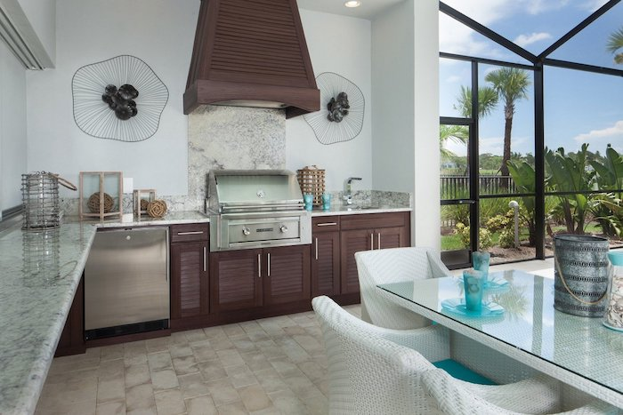 ein garten mit grünen pflanzen, eine küche mit einem waschbecken und elektroherd und einem ofen , ein weißer tisch und stühle aus rattan