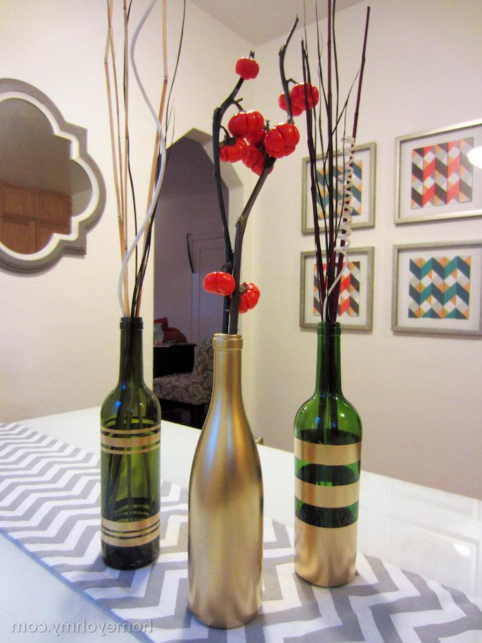 eine gldene alten weinflasche und zwei grünen alten flaschen, vasen aus flaschen selber basteln und mit pflanzen mit roten früchten, alte flaschen recyceln ideen