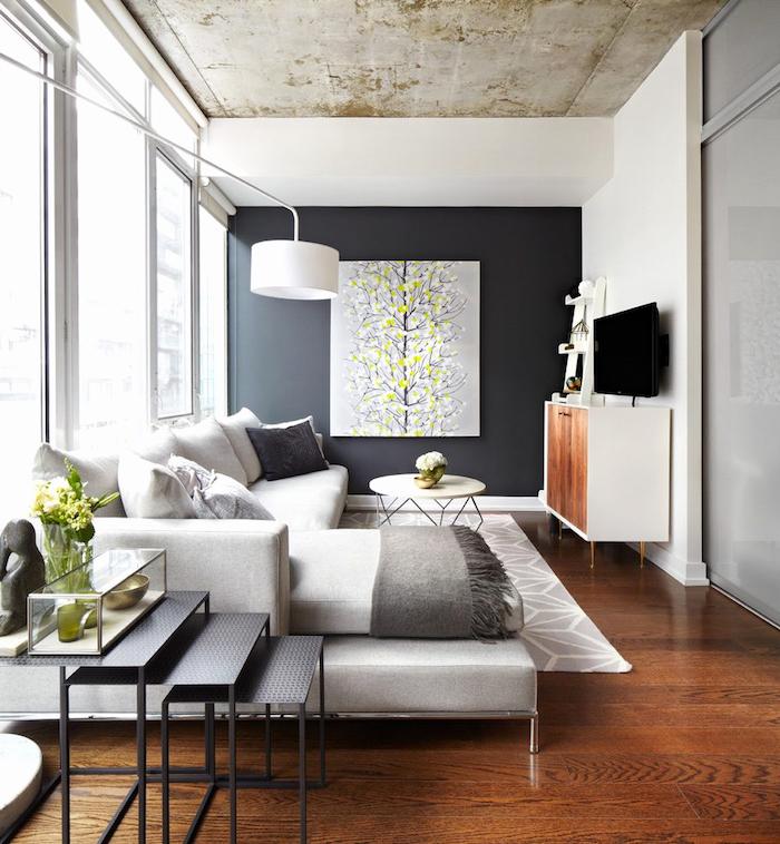 eine schwarze treppe und ein weißes sofa mit weißen und grauen kissen, eine schwarze wand mit einem grauen bild mit einem schwarzen baum mit weißen und gelben blumen und eine große weiße lampe, wandfarbe wohnzimmer